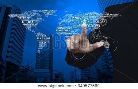 Businessman Pressing 2020 Start Up Business Flat Icon With Global Words World Map Over Modern Office