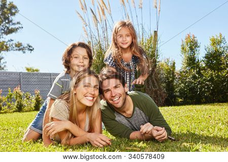 Happy parents and two kids in summer on vacation in nature on a meadow