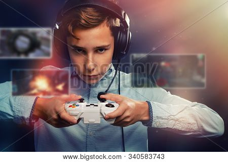 The Concept Of Video Games. A Teenage Boy, In Headphones With A Serious Look Playing A Game. In The