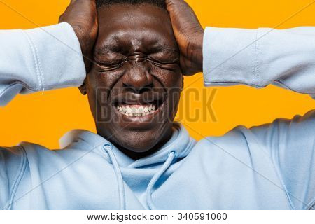 Image of tense african american guy in streetwear hoodie suffering and grabbing his head isolated over yellow background