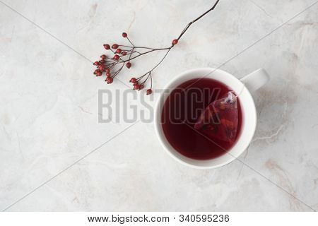 Fruity Tea In Tea Pyramid Bag In White Cup And Red Berries On Marble Background. Cozy Winter Mood, T