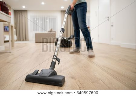 Wide Angle Photo Of Woman Housewife Or Maid Or Service Worker Hoovering With Vacuum Cleaner In Brigh