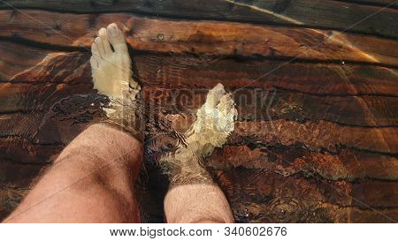 Naked Hairy Male Legs Walk On Pier. The Legs Of A Man Swim. First Person Of View. Men Rest On A Floo