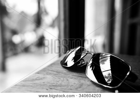 Single Simple Sun Glasses On The Wooden Table With Copy Space, Black And White Color