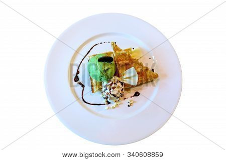 Dessert Made Of Brownie And Green Tea Ice Cream Together With Whipped Cream On The White Plate