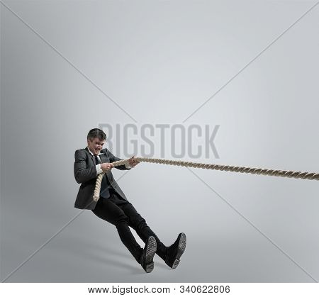 Time For Strenght. Man In Office Clothes Training With Ropes On Grey Background. Get Target, Overcom