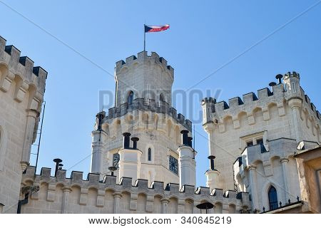 Czech Republic Flag On The Roof Of An Old Castle With Battlements And Clock On The Tower