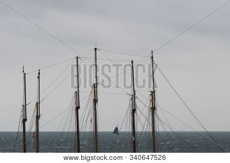 Sailboat In The Wadden Sea As Seen Through The Masts Of Two Three-masted Sailboats