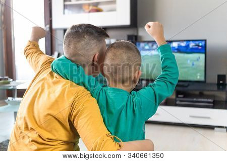 Kids, Two Boys Watching Soccer Game On Television, Cheering, Holding Their Arms Up In The Air