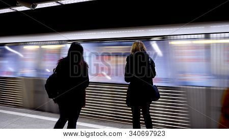 Photo Of Two Women Waiting At The Station For The Subway To Stop. Speed Or Rushing Concept. Rush Hou