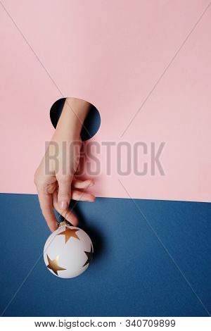 Close Up Of Human Hand Protruding Through Hole In Blue Background, Holding Gift.