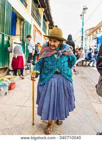 Cusco , Peru- Jan 9, 2019: Old  quechua woman with her caring bag in main street of  Cusco City, Peru.