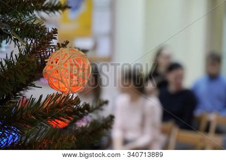 Christmas Tree Decorations On The Blured Background Of A Group Of People. Childrens Matinees And Hol