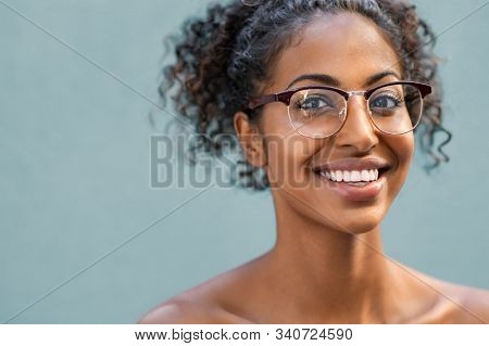 Cheerful young woman with wearing eyeglasses and looking at camera. Smiling african american woman wearing spectacles isolated against blue background. Portrait of happy black girl with copy space.