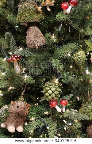 Vertical Image Of Holiday Tree Decorated In A Woodsy Them With Animals And Pine Cones.