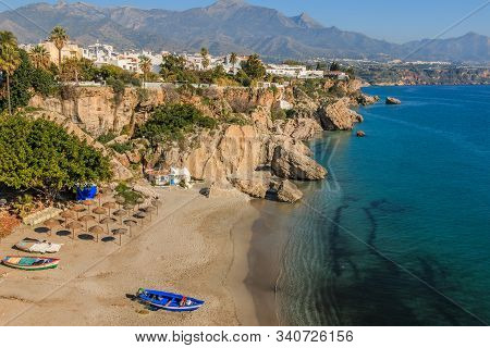 Beach Section In A Bay With Boats On The Spanish Costa Del Sol In Nerja. View Over The Place With Mo