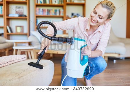 Cleaning lady with hand vacuum cleaner in the upholstered furniture vacuuming in the living room