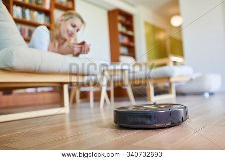 Vacuum robot vacuuming parquet floor in the living room