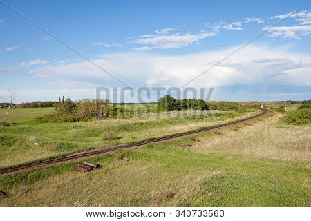 Railroad Track Curving Through Green Countryside Under Cloudy Blue Storm Sky