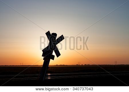 Railroad Crossing Sign On Prairie Silhouetted Against Sunrise Sky
