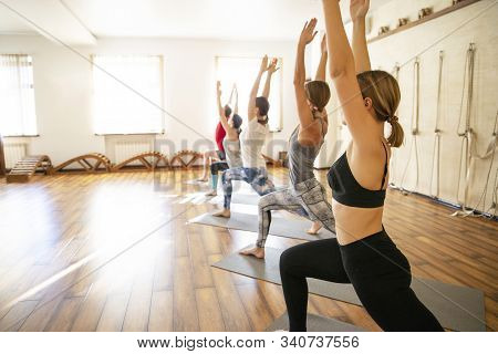 Yoga Class, Group Of People Relaxing And Doing Yoga Pose. Wellness And Healthy Lifestyle.