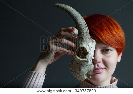 Portrait Of A Middle-aged Redhead Woman Holding Half A Goat Skull In Front Of Her Face, Duplicity Co