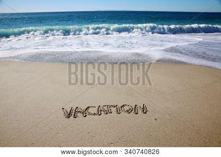 Vacation. Word VACATION written in the sand on the beach. Laguna Beach California. Words written in sand.