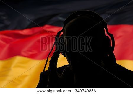 Silhouette Of A Man In Headphones On The Background Of The Flag Of Germany, Eavesdropping Conversati