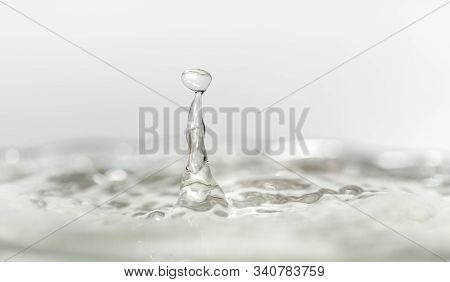 Droplet Of Water On Top Of Water Splash In White Background