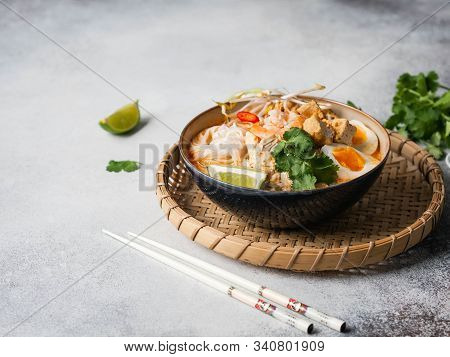 Malaysian Noodles Laksa Soup With Chicken, Prawn And Tofu In A Bowl On Grey Background. Copy Space
