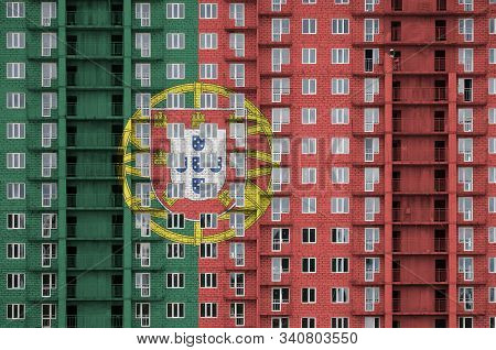 Portugal flag depicted in paint colors on multi-storey residental building under construction. Textured banner on brick wall background poster