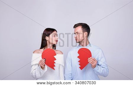 Cute Cute Gentle Sad Couple Of Lovers Look At Each Other, In The Hands Of Holding Halves Of A Broken
