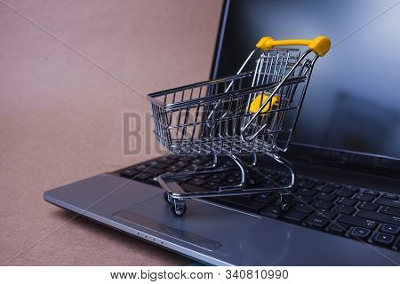 E-commerce, Concept. Online Shopping, Shopping Cart On Laptop Keyboard. Shopping In Online Stores An
