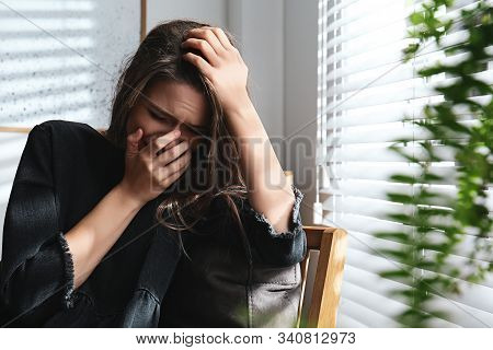 Abused Young Woman Crying Indoors. Domestic Violence Concept