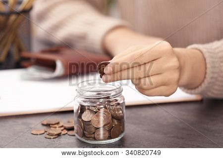 Woman Putting Money Into Glass Jar At Table, Closeup