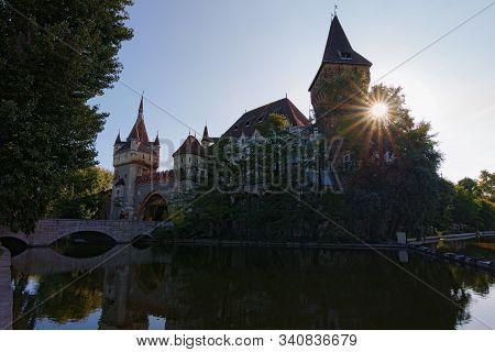 Wide Angle Landscape View Of Vajdahunyad Castle. City Park Of Budapest, Hungary. Sun Beams Shining,