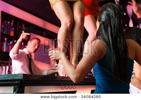People having a party in club or bar, two women are dancing on the table