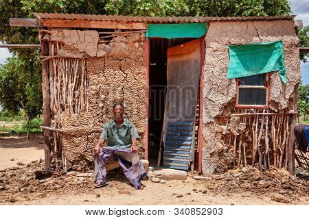 an old bushman man from Central Kalahari, village New Xade in Botswana, in front of his shack