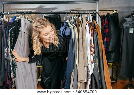 Shopping Blond Girl Is Shopping. Girl Chooses Clothes. Fashion. Concept - Clothes For Adult Girl. Pu