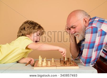 Chess Competition. Little Boy Playing Chess With Grandpa. Cute Boy Developing Chess Strategy. Childh