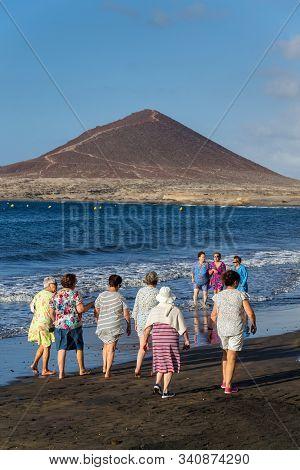 El Medano, Spain - July 9 2019: Senior Local Women Walking On Playa El Medano Beach During Sunrisee