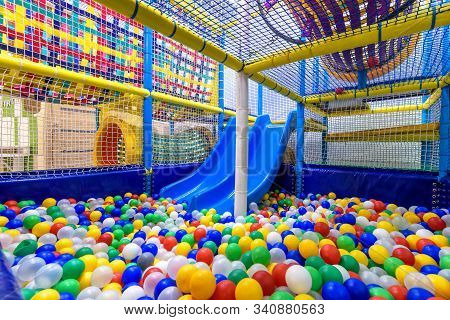 Kids Playground Indoor. Panoramic View Inside The Dry Pool With Colorful Balls And Slide. Nice Plast