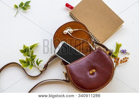 notebook planner , mobile phone for business work with hand bag leatherette collection of lifestyle woman and colorful  flowers arrangement flat lay style on background white poster