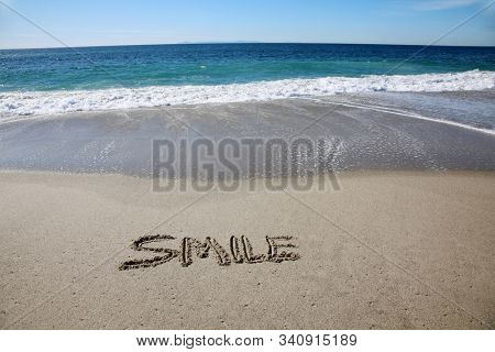 Smile. Words written in sand on the beach. The word SMILE written in the sand of Laguna Beach California with the pacific ocean background.