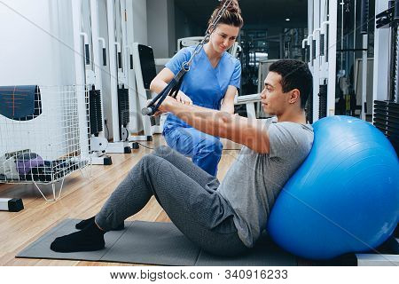 Kinesiologist Helps A Mixed Race Man Doing Exercises To Strengthen His Back Muscles. Treatment Of Ba