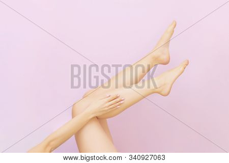 Beautiful Long Female Legs With Smooth Skin After Depilation On A Pastel Pink Background. The Concep