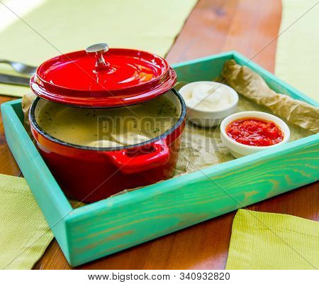 Red Pan With Ajar Lid On A Serving Plate With Two Sauces. Serving The First Course On The Served Tab