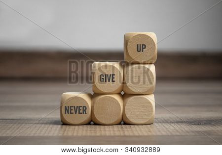 Pyramide Made Of Cubes And Dice With Message Never Give Up On Wooden Background