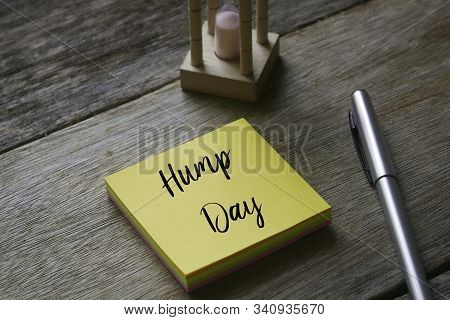 Sand Clock,pen And Yellow Sticky Notes Written With Hump Day On Wooden Background.