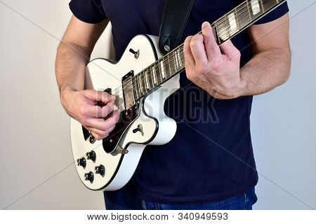 Man Playing A White Electric Guitar With Humbucker Pickups.